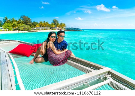 Portrait of happy loving couple at beautiful water villa at Maldives island. Travel and Vacation. Outdoor shot #1110678122