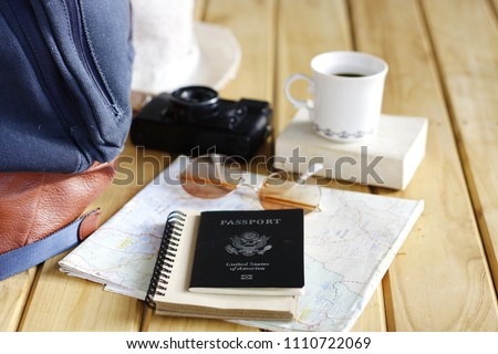 US passport and Travel Equipment on a Wood Table Stock image Vintage cameras, maps, glasses, translation books, passports, travel, travel destinations #1110722069