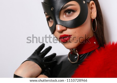 Beautiful dominant brunette vamp mistress bdsm girl with fashion makeup in glamour latex dress, collar and bdsm black leather fetish rabbit mask posing on white background #1110728966