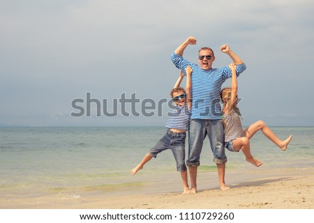 Father and kids playing on the beach at the day time. They are dressed in sailor's vests. Concept of sailors on vacation and friendly family. #1110729260