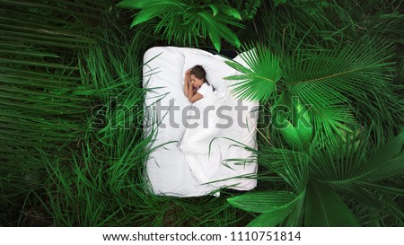 A hidden place. Sleeping woman in deep jungle forest lies on airbed,View from above #1110751814