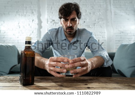 drunk alcoholic lain business man drinking whiskey from the bottle and glass depressed wasted and sad at home couch in alcohol abuse and alcoholism concept #1110822989