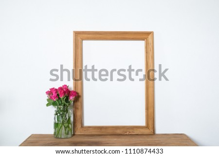 Vintage frame with pink rose flowers on wooden table