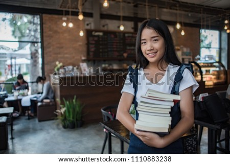 Smiling young woman holding books #1110883238