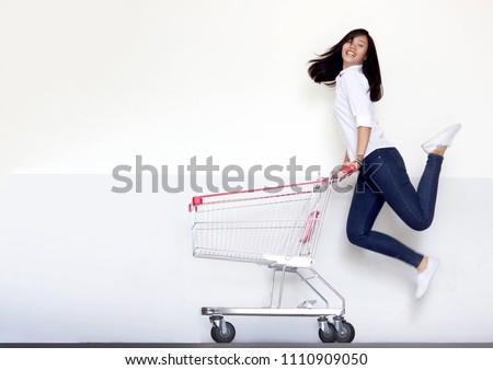 happy shopping asian girl jumping with shopping cart on white background. Shopping girl with casual suite portrait action model for marketing concept. #1110909050