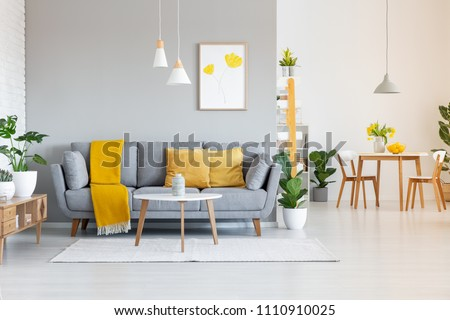 Orange blanket on grey sofa in modern apartment interior with poster and wooden table. Real photo
