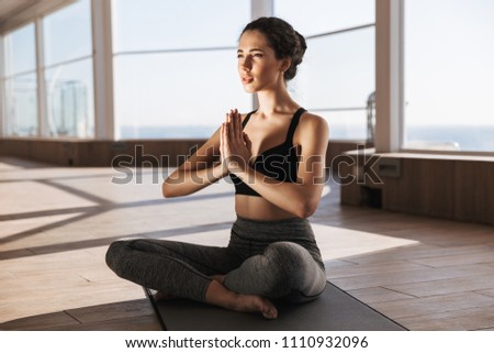 Portrait of a healthy young sportswoman doing yoga exercises at the gym while sitting on a fitness mat #1110932096
