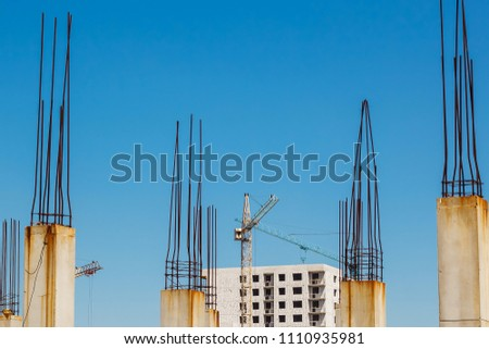 Exterior of unfinished building construction and building cranes against blue sky background. Modern technologies and civil engineering. Square section piles with prestressed reinforcement. #1110935981