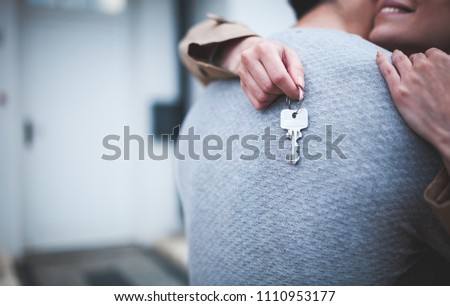 Young woman holding keys hugging husband in front of their new home after buying real estate #1110953177