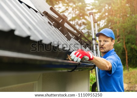 worker cleaning house gutter from leaves and dirt #1110955250