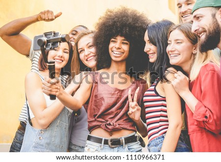 Happy millennials friends making video feed with smartphone outdoor - Young people having fun with new technology trends - Youth lifestyle and social media concept - Focus on black african girl face #1110966371