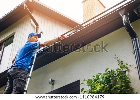man on ladder cleaning house gutter from leaves and dirt #1110984179