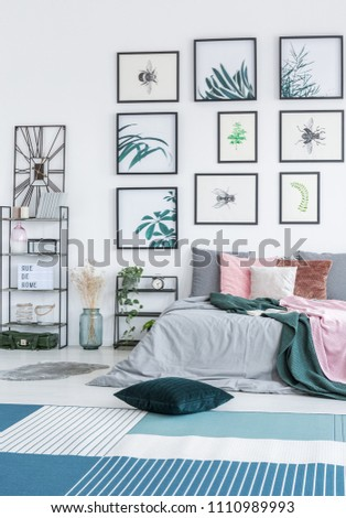 Green cushion placed on the floor with blue and white carpet in bright bedroom interior with double bed, two metal racks with plants and simple gallery of posters hanging on the wall #1110989993