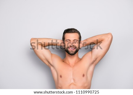 Attractive, stunning, manly, smiling macho isolated on gray background, having two arms behind the head and closed eyes, showing his shaven armpits - wellness, wellbeing concept #1110990725