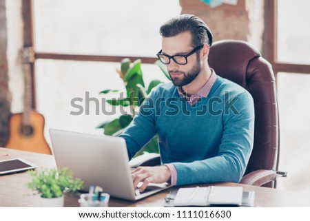 Stunning man in shirt and pullover sitting on leather chair at desktop in work station, with concentrated expression looking at screen of laptop, searching information, works on project, presentation #1111016630