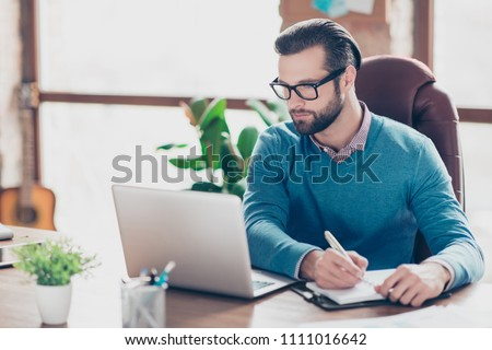 Stunning, virile, harsh, concentrated lawyer in shirt and pullover making notes in his notebook, organizing his day, sitting on leather chair at desktop in work station #1111016642