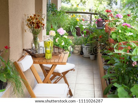 Beautiful terrace or balcony with small table, chair and flowers. Summer time Idyllic seating in the terrace with drink. Royalty-Free Stock Photo #1111026287