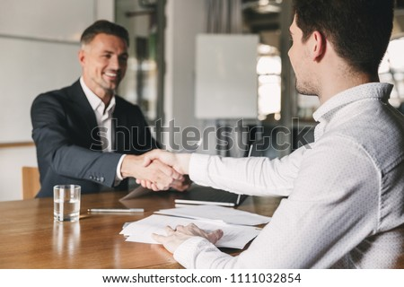 Business, career and placement concept - successful young man smiling and handshaking with european businessman after successful negotiations or interview in office #1111032854