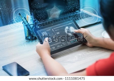 Hands of woman using tablet on wooden table with HUD user interface and dot connection for cyber futuristic concept #1111081475
