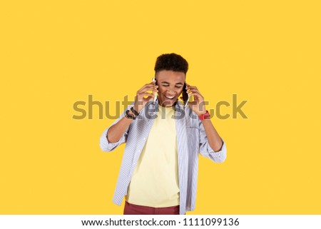 Interesting experience. Joyful positive man laughing while putting both phones to his ears #1111099136