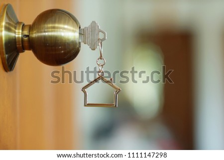 Home key with metal house keychain in keyhole, property concept #1111147298