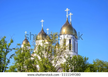 Golden-domed domes of the Cathedral of Christ the Savior and the chapel of Peter and Fevronia against the blue sky in the city of Kaliningrad #1111149380