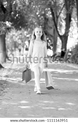 Girl with shopping bags walk in park. Child with paper bags in summer. Kid shopper in fashion clothes outdoor. Little princess with crown on long blond hair. Shopping on sale and purchase. #1111163951