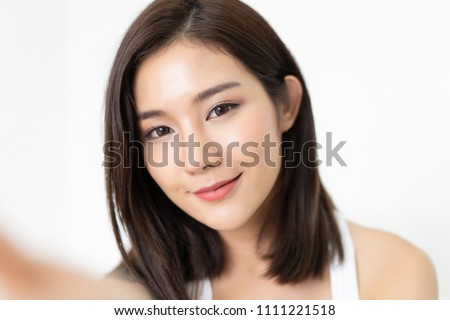 Close-up of young Asian beautiful woman taking selfie. Isolated white background.Beauty and Healthy Woman.