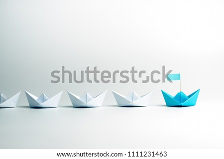 Leadership concept. Blue leader paper ship leading among white on white background. #1111231463