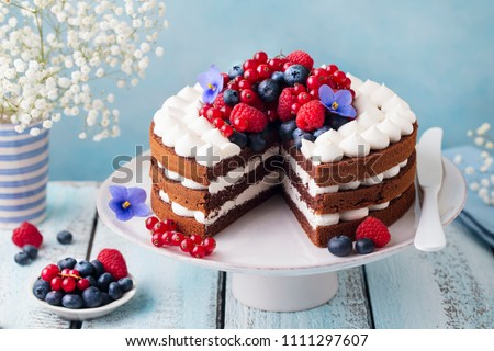 Chocolate cake with whipped cream and fresh berries. Blue wooden background. Close up. #1111297607