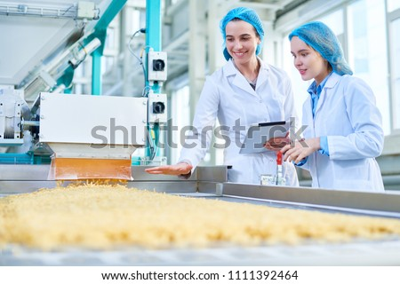 Waist up portrait of  two young female workers wearing lab coats standing by  conveyor line with macaroni  in clean production workshop, copy space #1111392464