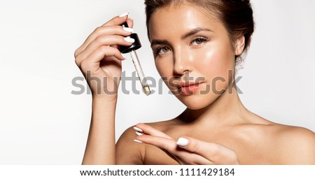 Portrait of  young woman with fresh perfect skin posing at studio. Glorious girl applying liquid oil for skincare. Cosmetology and treatment concept. Isolated on grey background #1111429184