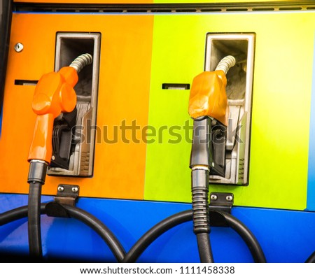 Gas pump nozzles in a service station with sunlight  #1111458338