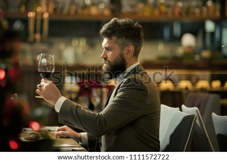 man is tasting the wine. Romantic dinner. young man standing and holding wineglasses #1111572722
