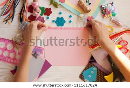 Woman's hand cut paper, scrapbooking for wedding or other festive decorations . Tools for scrapbooking. Royalty-Free Stock Photo #1111617824