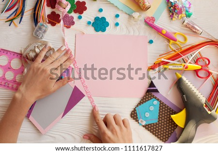 Woman's hand cut paper, scrapbooking for wedding or other festive decorations . Tools for scrapbooking. Royalty-Free Stock Photo #1111617827