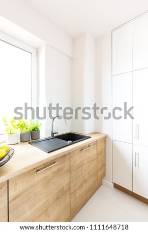 Black sink in wooden countertop in white kitchen interior with window. Real photo #1111648718