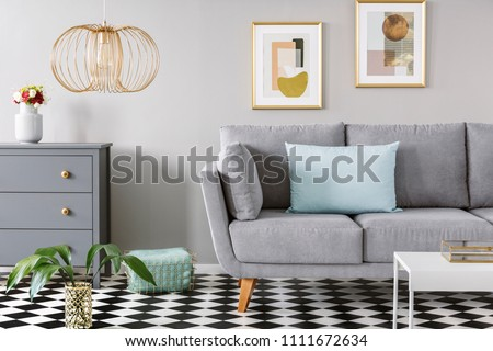 Light blue pillow placed on grey couch in bright living room interior with checkerboard linoleum floor, fresh flowers in vase on cupboard, two posters hanging on the wall and gold lamp #1111672634