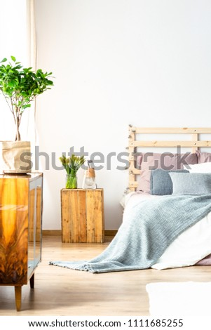 Real photo of a bed standing next to a small wooden table in a minimal bedroom interior with a cupboard and a plant on it #1111685255