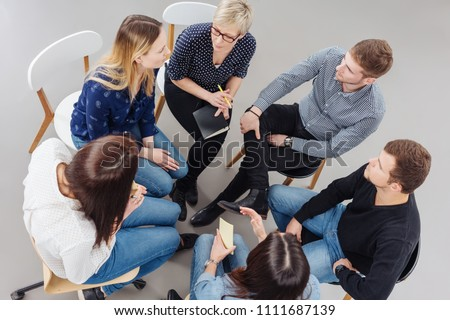 Group of people having a meeting together seated in a tight circle in a view from above Royalty-Free Stock Photo #1111687139