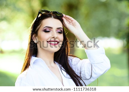 Cute young brunette girl with beautiful professional make-up on green background in park. #1111736318