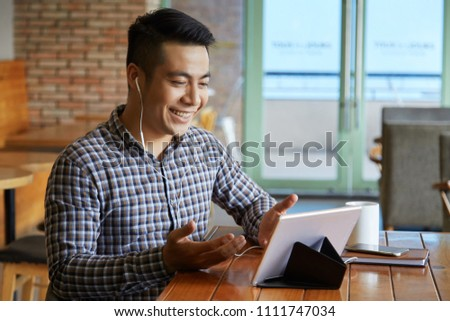 Smiling Asian man wearing headphones and communicating on tablet #1111747034