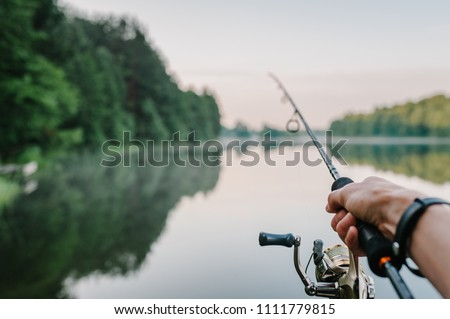 Fisherman with rod, spinning reel on the river bank. Sunrise. Fishing for pike, perch, carp. Fog against the backdrop of lake. background Misty morning. wild nature. The concept of a rural getaway. Royalty-Free Stock Photo #1111779815
