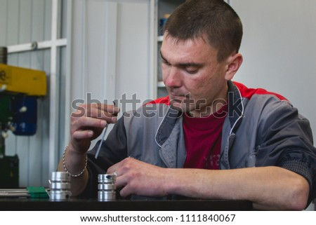 Male worker manually assembles metal detail for CNC machine at factory with lathes #1111840067