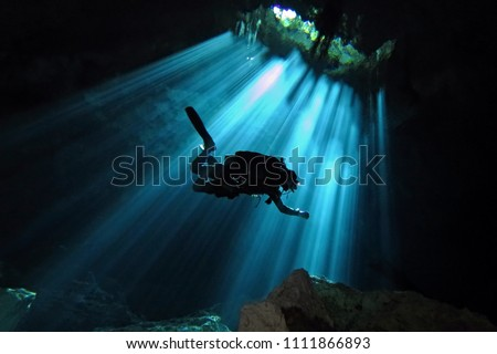 Technical scuba diver exploring underwater cenote. Scuba diver in the sun light from the water surface. Underwater dark cave and diver. Royalty-Free Stock Photo #1111866893