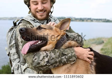 Man in military uniform with German shepherd dog outdoors #1111893602