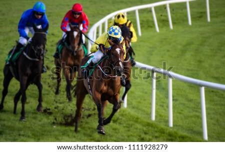 Galloping race horses and jockeys racing around the corner of the track #1111928279