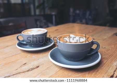 Closeup image of two blue cups of hot latte coffee on vintage wooden table in cafe #1111968884