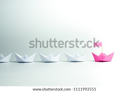 Woman leadership concept with pink paper ship leading among white on white background. #1111992551