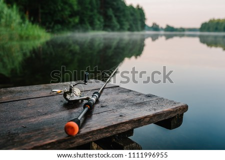 Fishing rod, spinning reel on the background pier river bank. Sunrise. Fog against the backdrop of lake. Misty morning. wild nature. The concept of rural getaway. Article about fishing day. #1111996955